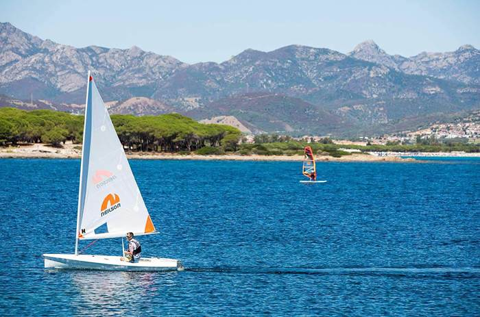 A man sailing a Neilson branded sail boat at Neilson Baia De Mori Beachclub in Sardinia