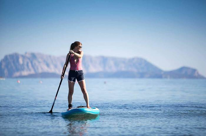 A woman stand up paddleboarding on the sea at Neilson Baia De Mori Beachclub in Sardinia