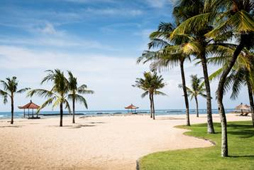 palm trees and a strip of sand leads you to the sea from Club Med Bali