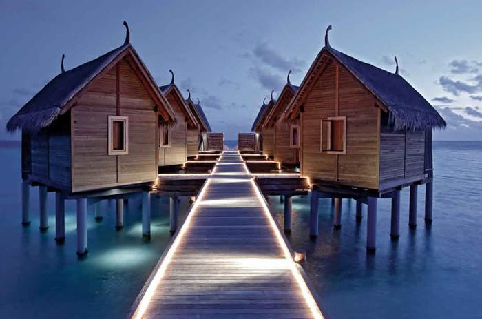 Overwater villas at night at constance moofushi maldives resort