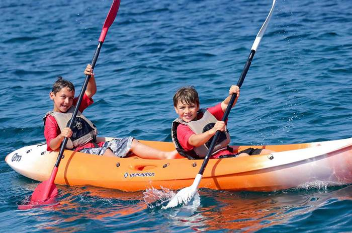 two children laughing and kayaking at Neilson Alana Beachclub in Croatia