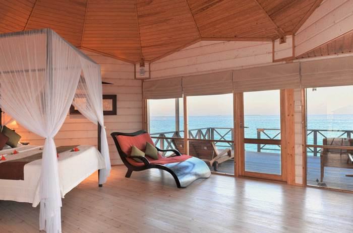 A four poster bed looking out over the sea at Kuoni Komandoo Island and Spa in the Maldives