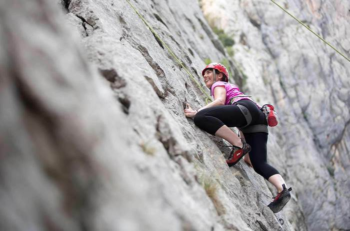A woman smiling and climbing a sheer rock face at Neilson Alana Beachclub in Croatia
