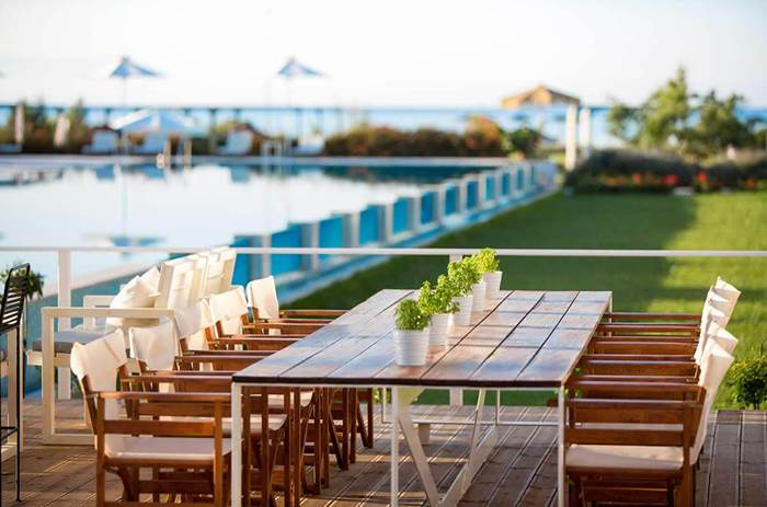A view of the outside dining tables and pool at Neilson Buca beach resort in Greece