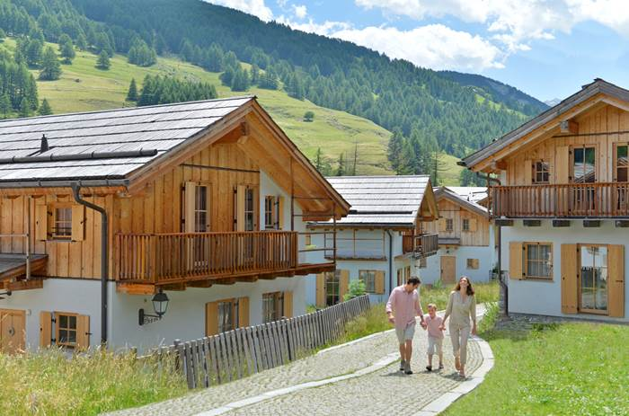 A family strolling through the accommodation in summer at Club Med Pragelato Vialetta