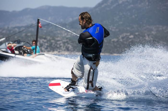A man Wakeboarding at a Neilson Beachclub Resort